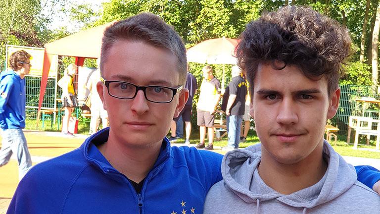 Tim Tanner und Ron Yücel stehen nebeneinander; sie sind beide deutsche Meister im Murmeln.