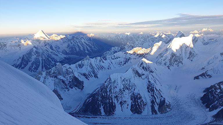 Schatten des Broad Peak fällt auf Berge des Karakorums