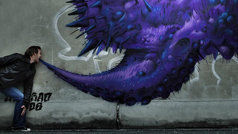 Ein Mann, der vor einer lilanen Graffito-Wolke steht, symbolisiert Mundgeruch.