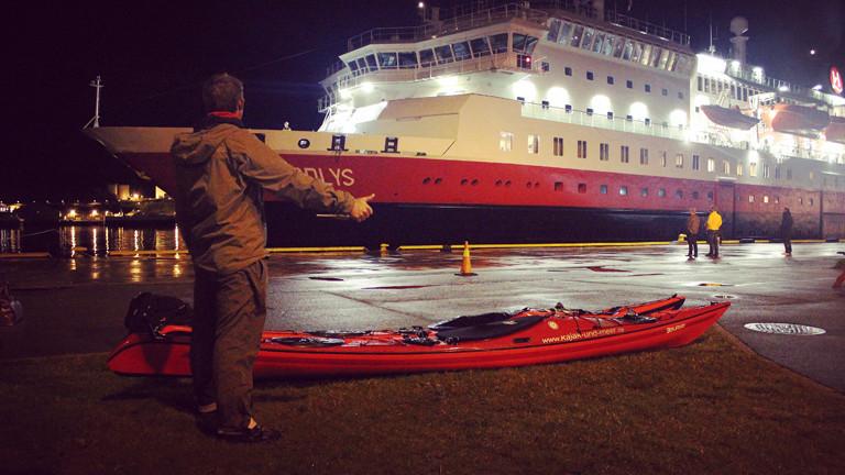 Kajak vor großem Schiff, Mann hält Finger raus