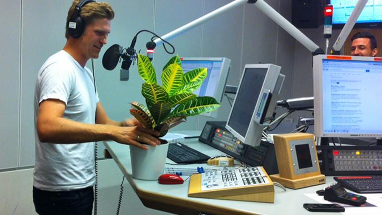 Moderator Thilo Jahn inspiziert eine Topfpflanze.