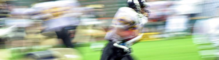 Szene beim American Football. Spieler rennen umher, sie sind stark unscharf. Im Vordergrund rennt ein Spieler mit dem Ball unterm Arm.