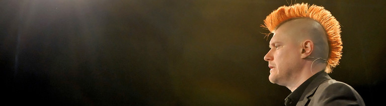 Sascha Lobo bei einem Vortrag. Er hat einen orangen Irokesen-Haarschnitt und trägt einen schwarzen Anzug. Er ist im Profil aufgenommen. Der Hintergrund ist schwarz; Bild: dpa | Britta Pedersen