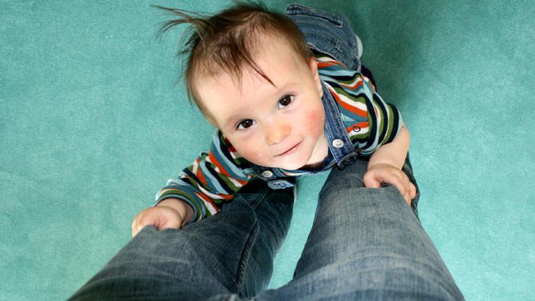 Ein Kind hält sich an den Hosenbeinen seiner Mutter fest.