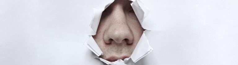 Eine Nase, die durch ein zerrissenes Papier durch zu sehen ist.