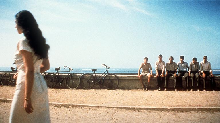 Junge Männer blicken einer Frau hinterher.