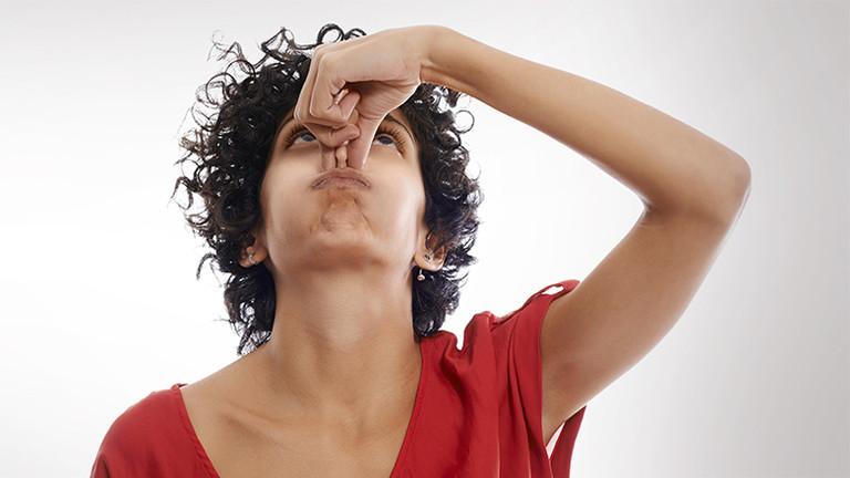 Eine Frau hält sich mit zwei Fingern die Nase zu.