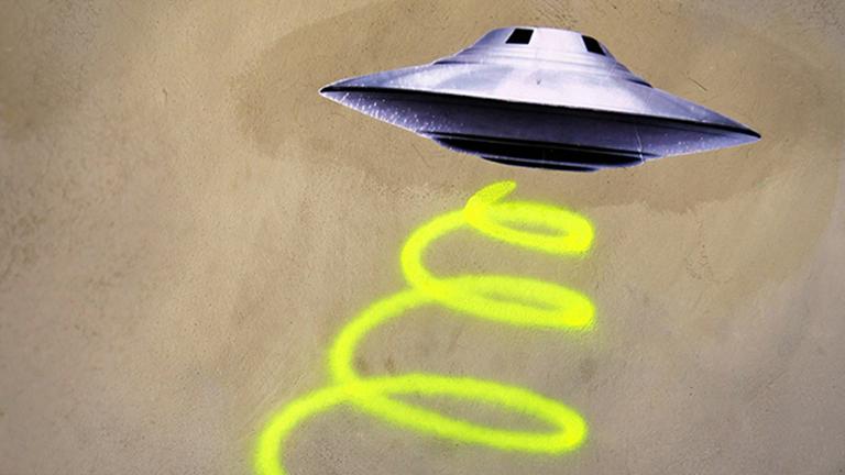 Ein Ufo ist als Graffiti auf eine Wand gemalt.