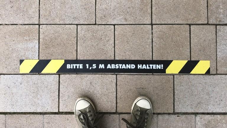 1,5 Meter Abstand halten Hinweis auf der Straße.
