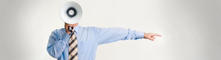 Ein Mann deutet in eine Richtung und hält ein Megaphon vor seinem Gesicht.