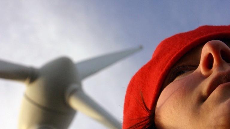 Eine Frau mit roter Mütze - im Hintergrund ein Windrad.