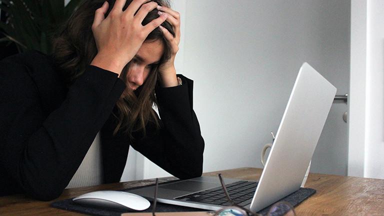 Eine junge Frau stützt vor ihrem Laptop verzweifelt die Hände in den Kopf.