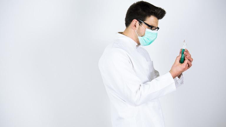 Junger Arzt mit Mundschutz und Spritze