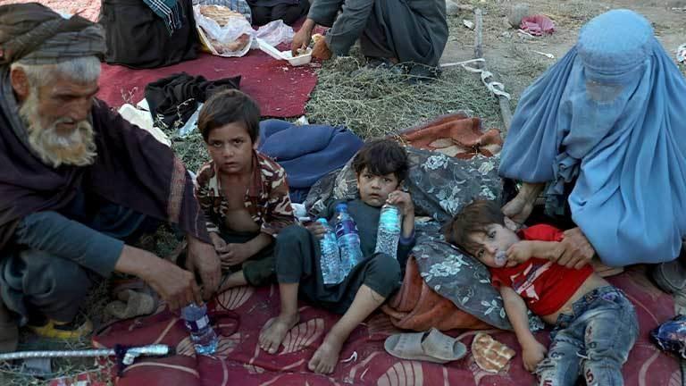 Eine Frau, drei Kinder und ein alter Mann sitzen im Freien.