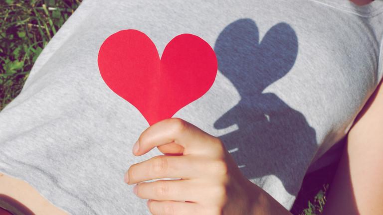 Frau hält ein Herz in der Hand.