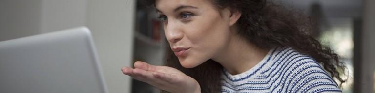 Frau vor dem Laptop, die eine Kusshand Richtung Bildschirm schickt.