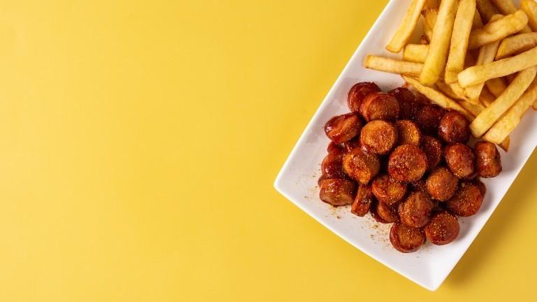 Ein Teller mit Currywurst und Pommes