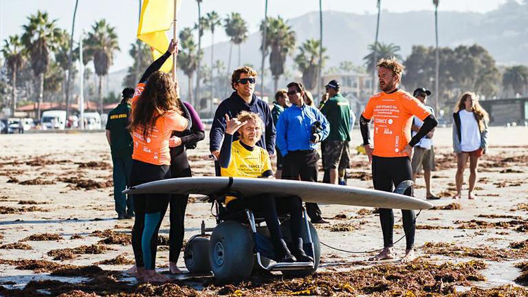 Mann mit Rollstuhl und Surfboard.