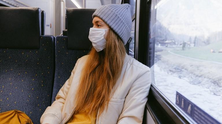 Frau mit Mundschutz und Mütze in einem Zug.