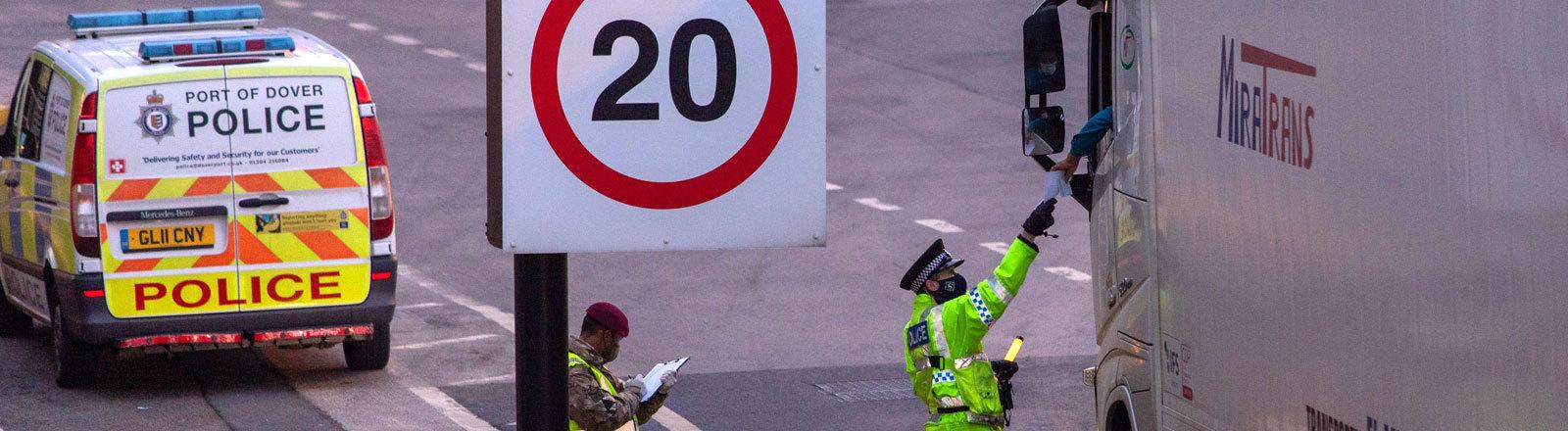 Ein Polizist checkt Dokumente eines LKW in Dover.