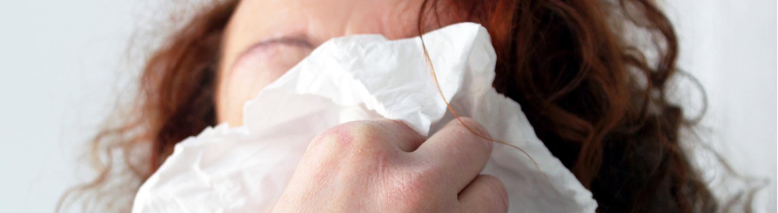 Frau hält ein Taschentuch in der Hand.