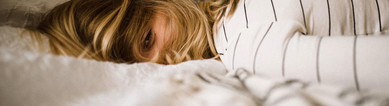 Eine Frau liegt mit offenen Augen auf dem Bauch auf einem Bett.