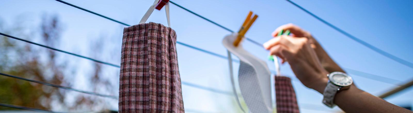 Mann hängt Mundschutz zum Trocknen an die Wäscheleine
