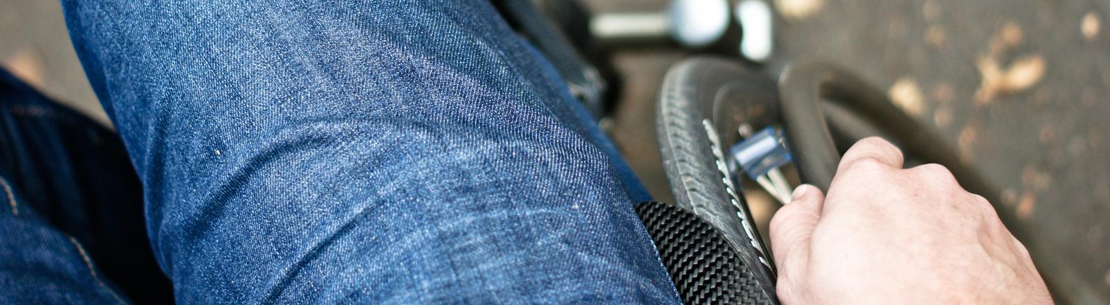 Mann im Rollstuhl, Detailaufnahme von seiner Hand am Rad.