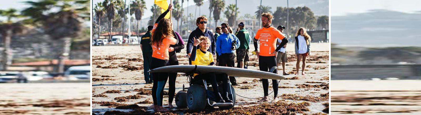 Mann mit Rollstuhl und Surfboard