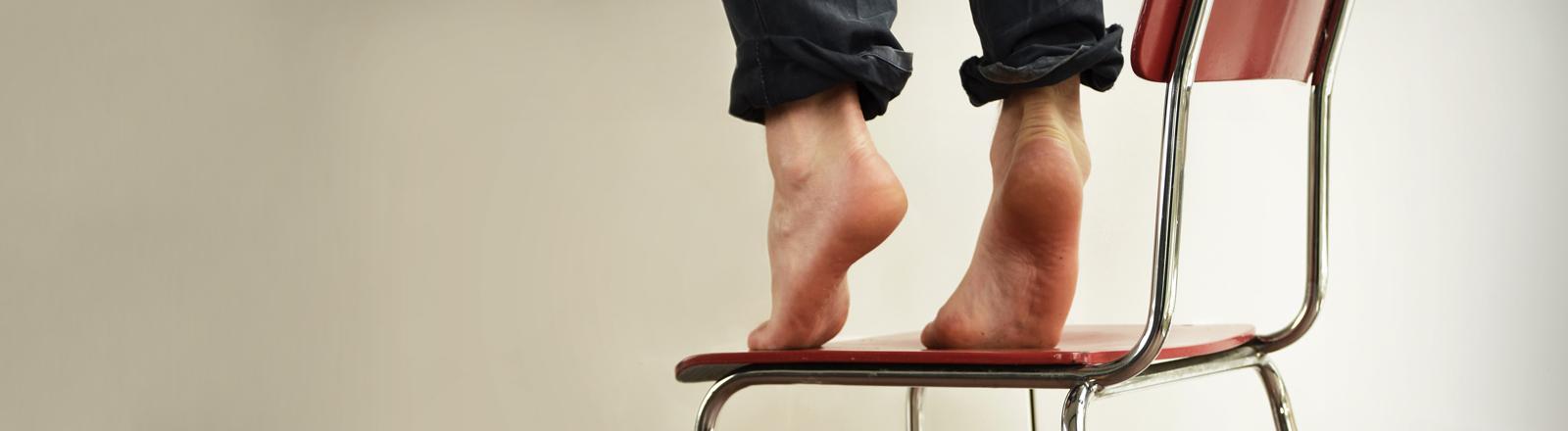 Zwei Füße auf einem Stuhl, auf den Zehenspitzen stehend