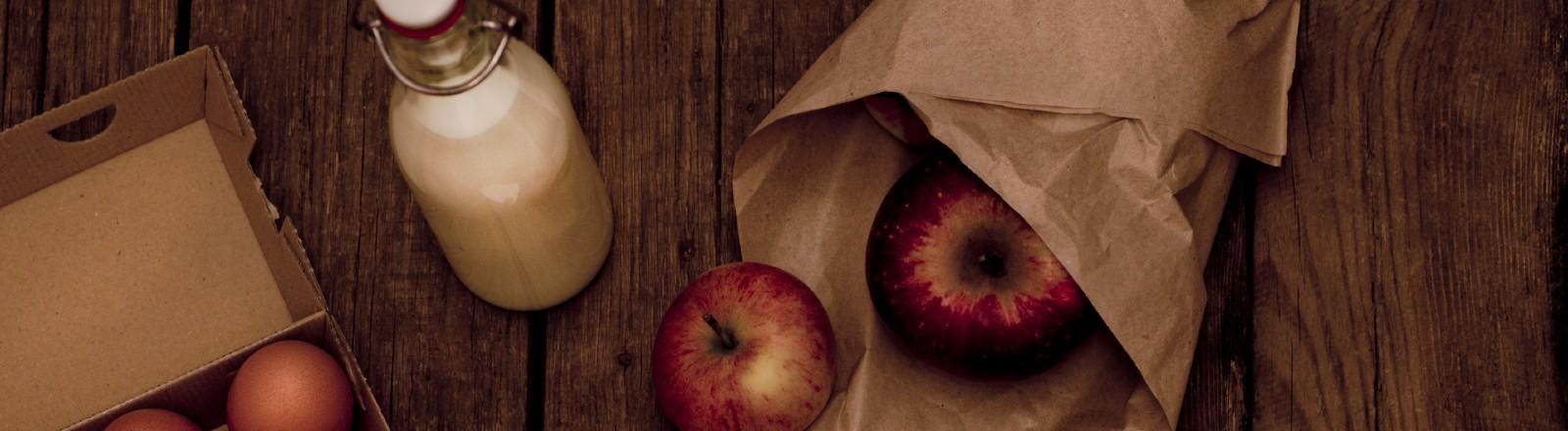 Eier, Milch und Äpfel liegen auf einem Holztisch.