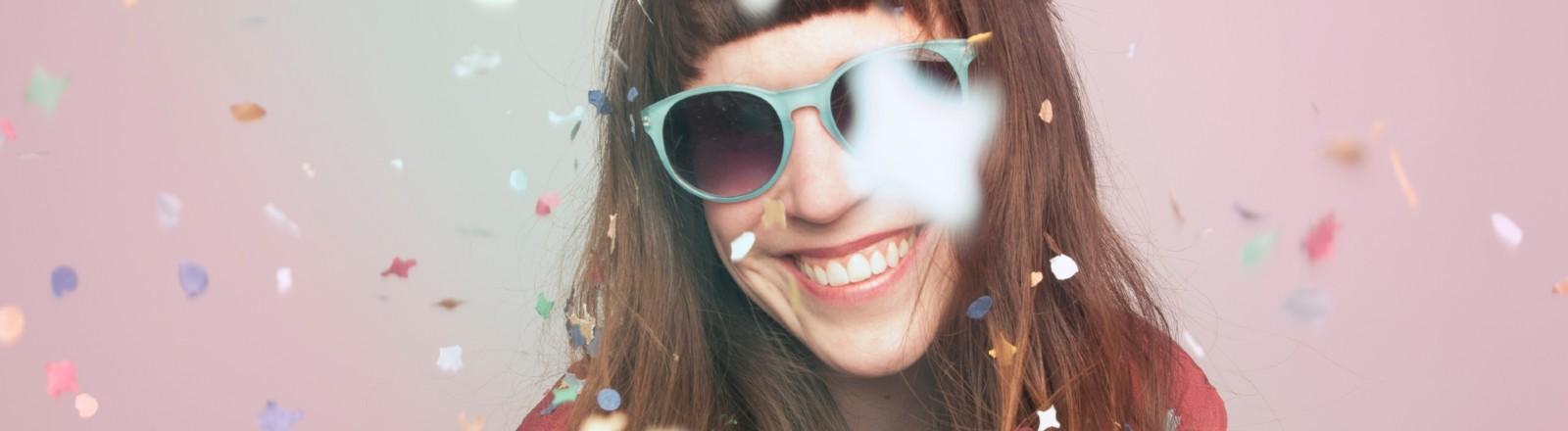 Junge Frau mit Konfetti im Gesicht.