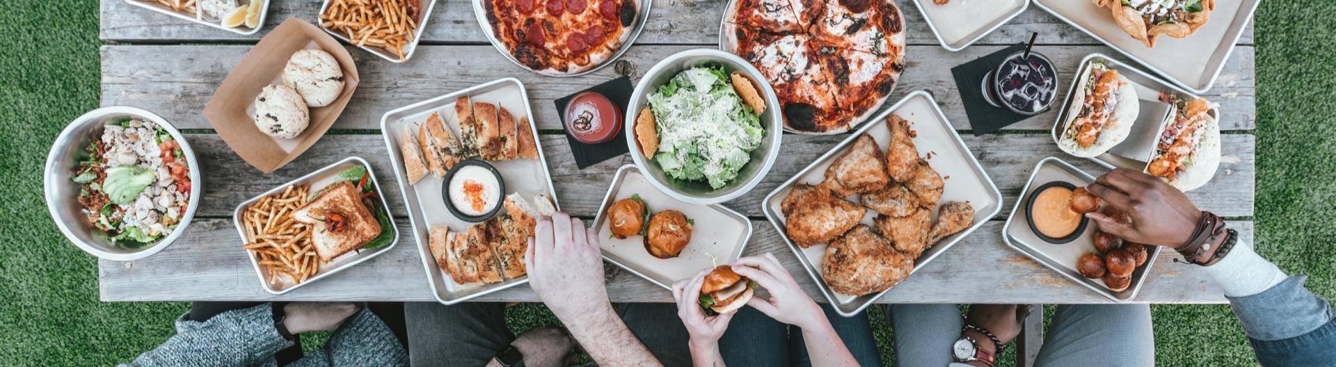 Langer Tisch auf dem Pizza, Burger, Pommes und weiteres Fastfood stehen und Leute sich bedienen