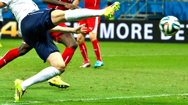 Ein Fußballer schießt den Ball.