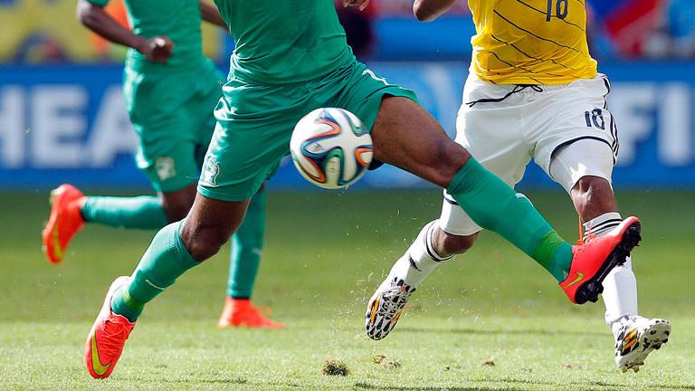 Drei Fußballer laufen dem Balll hinterher.