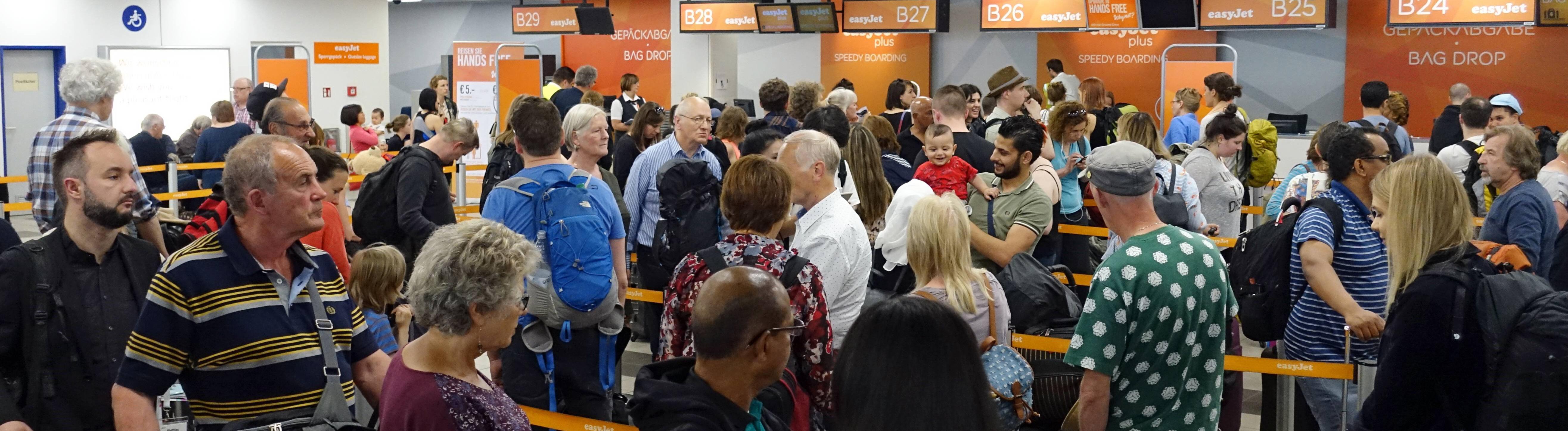 Flugpassagiere stehen am Check-in von easyJet am Flughafen Berlin-Schoenefeld an. (abfertigen, Abfertigung,