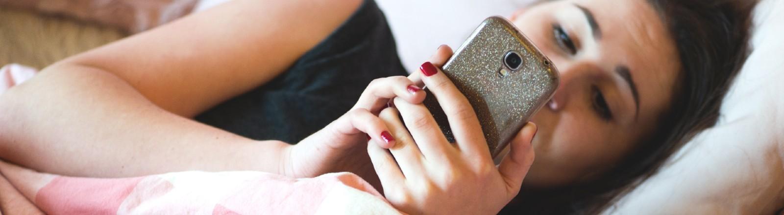 Junge Frau liegt im Bett und schaut auf das Handy.