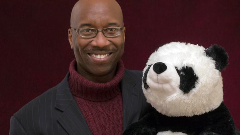 Mann mit Anzug und Plüsch-Pandabär im Arm.