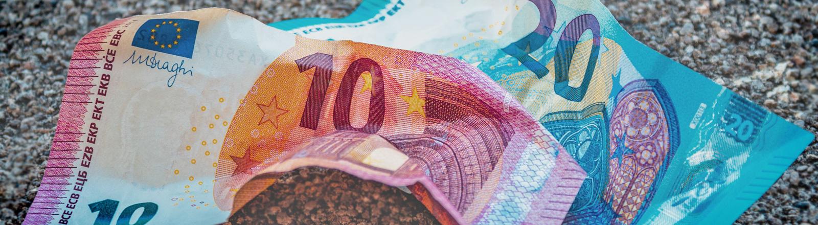 Ein 10-Euro-Schein und ein 20-Euro-Schein liegen zerknüllt auf dem Boden
