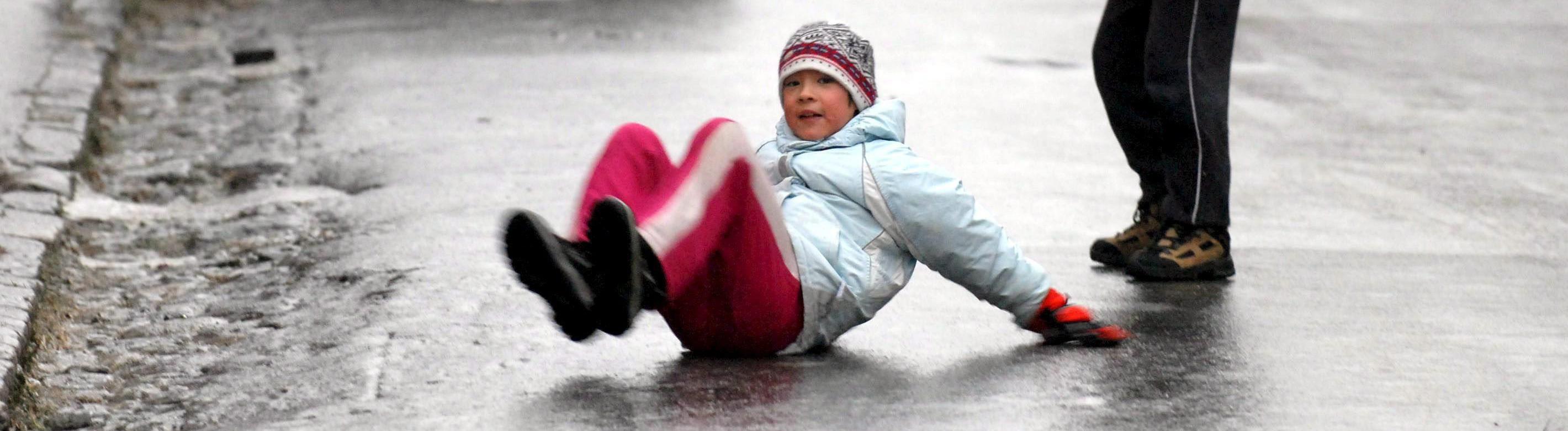 Kinder schlittern über eine gefrorene Straße.