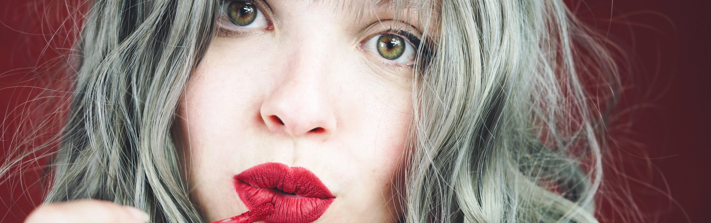 Junge Frau mit grauen Haaren schminkt sich Lippen
