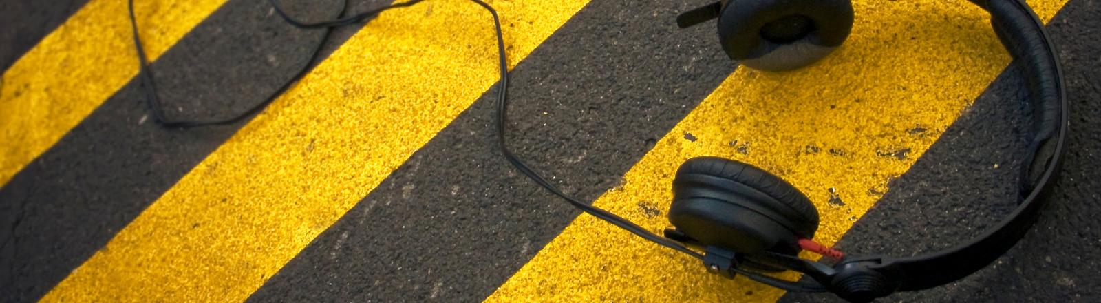 Kopfhörer liegen auf einer Straße mit gelben Zebrastreifen.