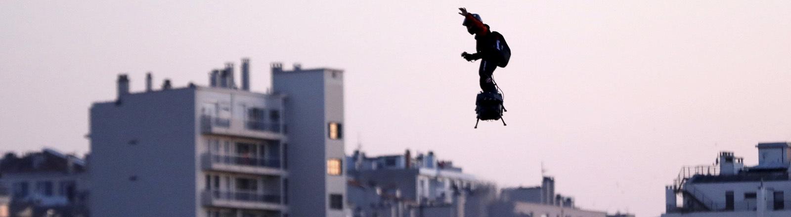Mann auf einem Flyboard über den Dächern von Paris