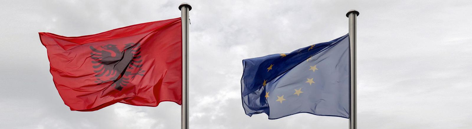 Die Flaggen von Albanien und der EU wehen im Wind - der Himmel ist bedeckt.