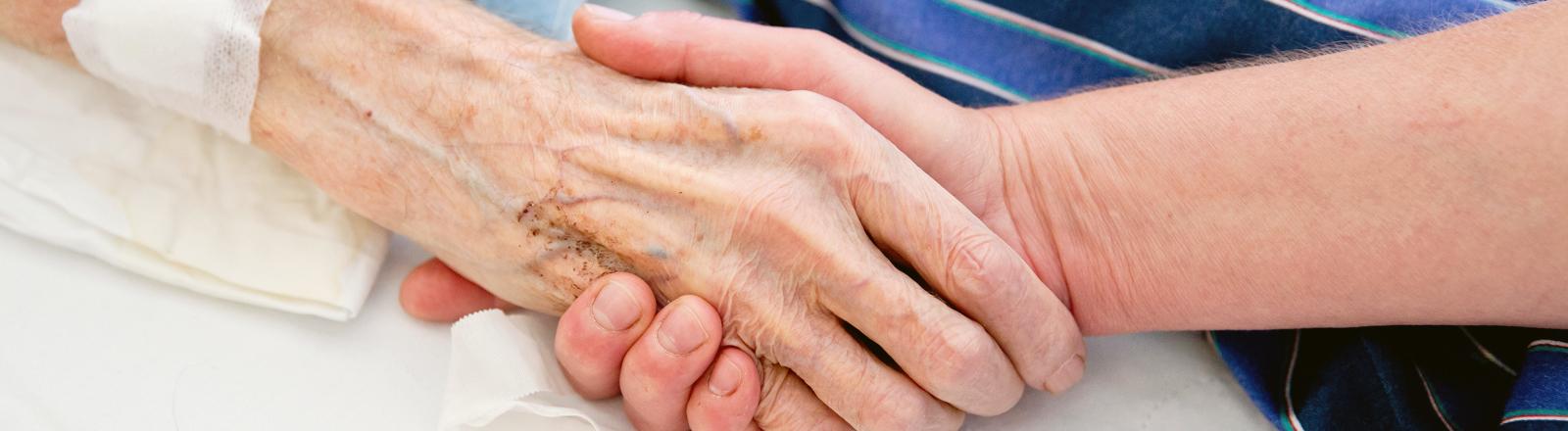 Ein junger Mann hält die Hand einer alten Frau im Krankenhaus.