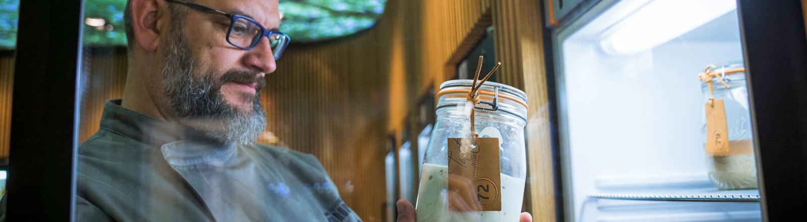 Karl de Smedt schaut auf ein Einmachglas, in dem Sauerteig ist.