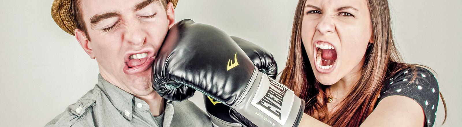Eine Frau schreit und boxt mit einem Boxhandschuh einem Mann ins Gesicht.
