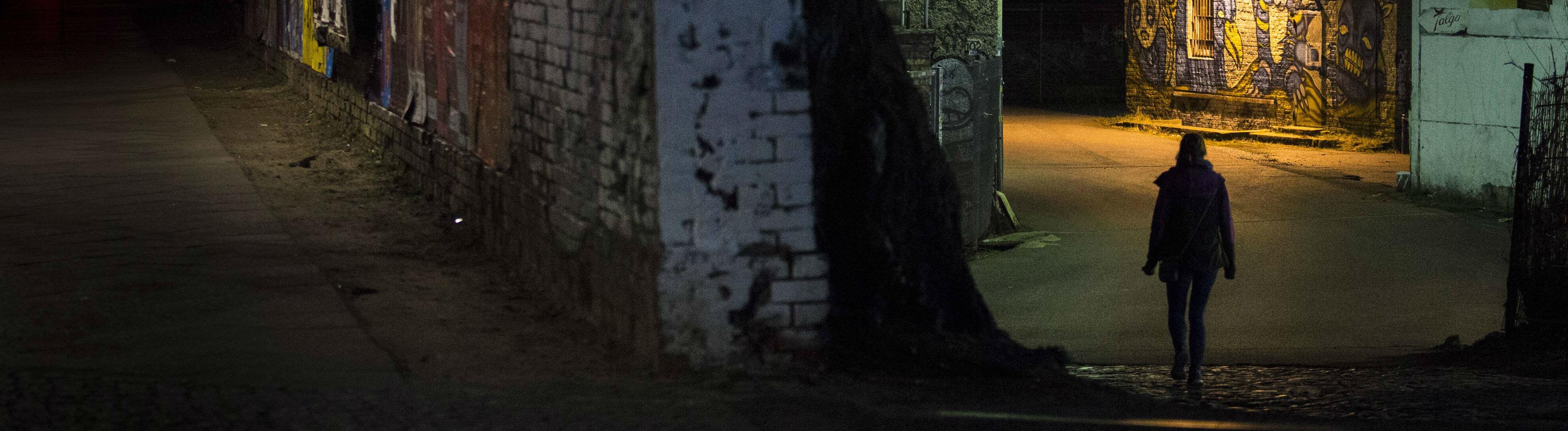 Eine Frau laeuft nachts allein entlang einer karg beleuchteten Strasse in Berlin.
