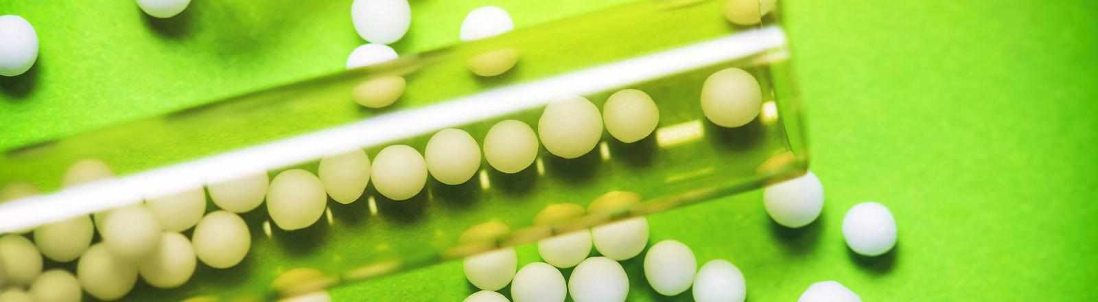 Globuli, homöopathisches Arzneimittel in einem Röhrchen auf grünem Hintergrund.