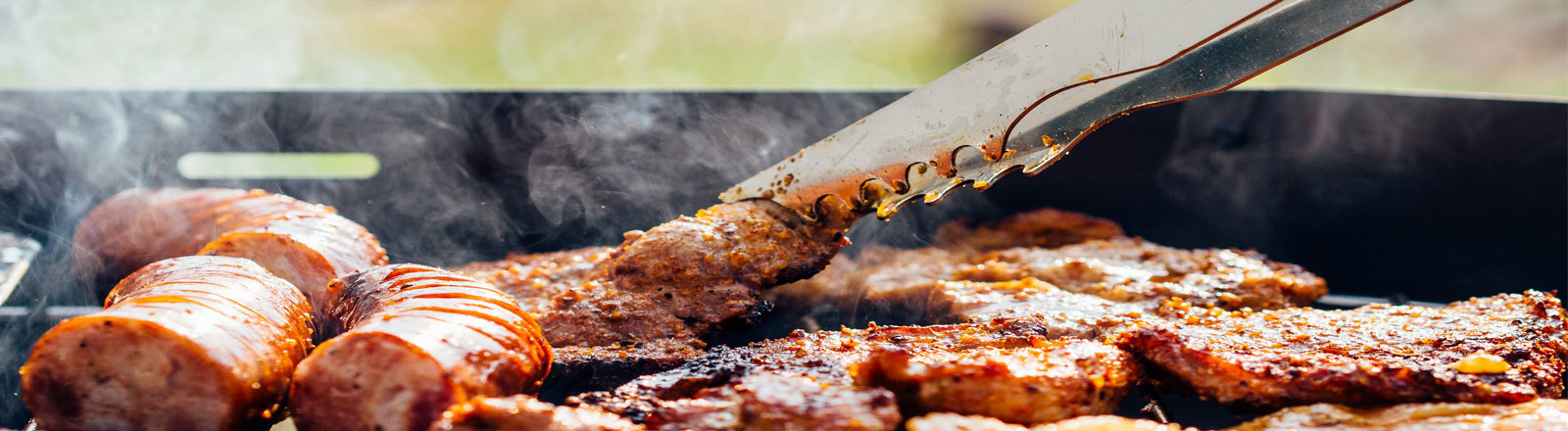 Ein großer Kugelgrill mit vielen verschiedenen Fleischstücken drauf. Es dampft.